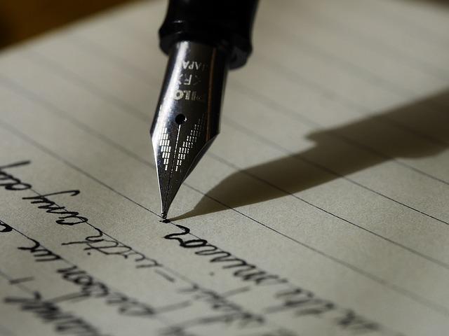 Detalhe de foto mostrando uma caneta escrevendo palavras em um caderno